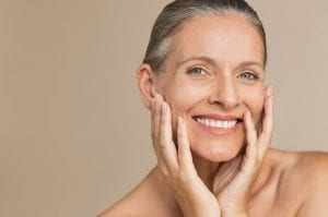 mature woman smiling with hand on face. Closeup face